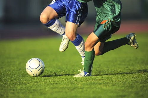 Two soccer players chasing a ball