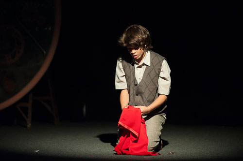 Student actor alone on stage under spotlight