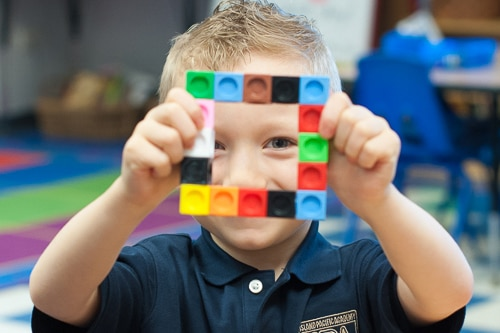 Little boy looking through a square of blocks