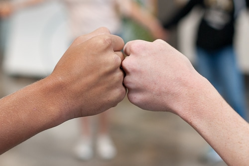 Two students bumping fists