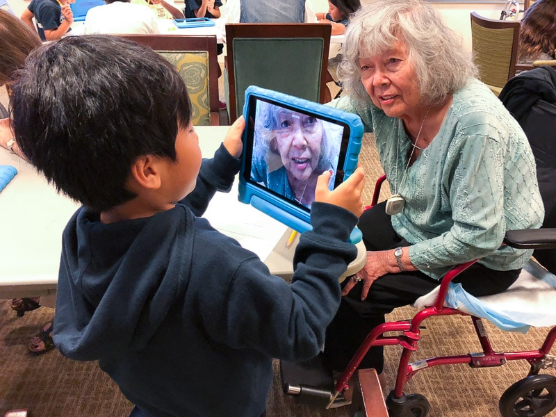 Grade 2 student takes picture of senior on iPad