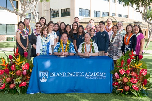 Heads of School for Kamehameha and Island Pacific Academy signing document with students behind them.