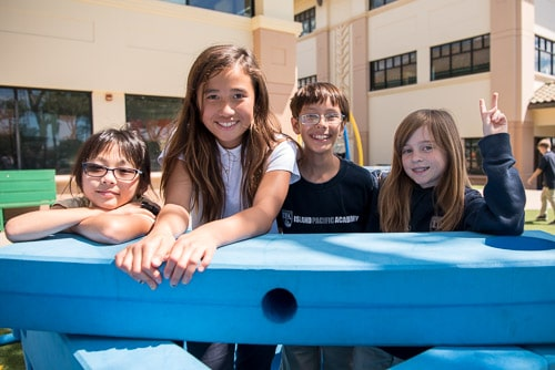 Four elementary students playing with big blue blocks