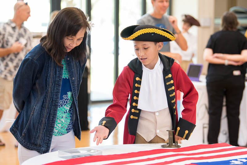 Student in red coat costume explains flag display to a museum visitor