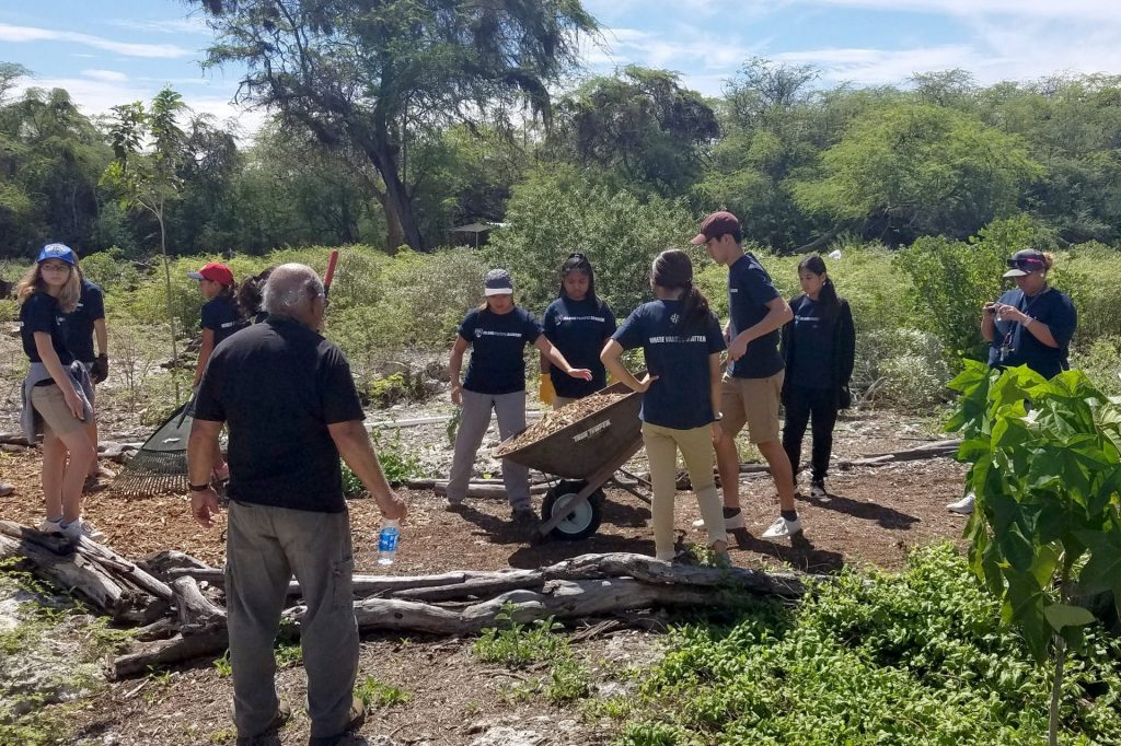 IPA students move dirt with wheelbarrow during community service project