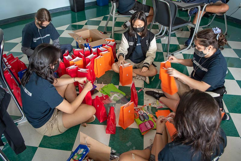 Students sitting in a circle filling treat bags