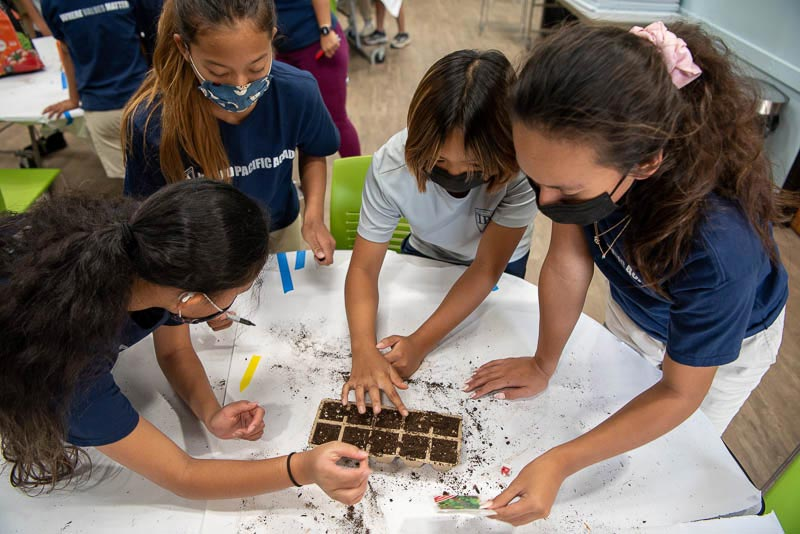 Students around a table planting seeds in soil
