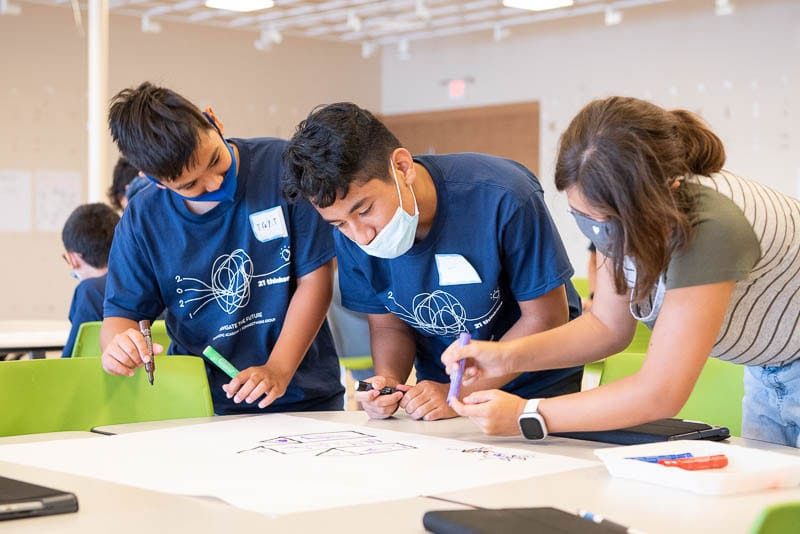 Three students working together around a table.