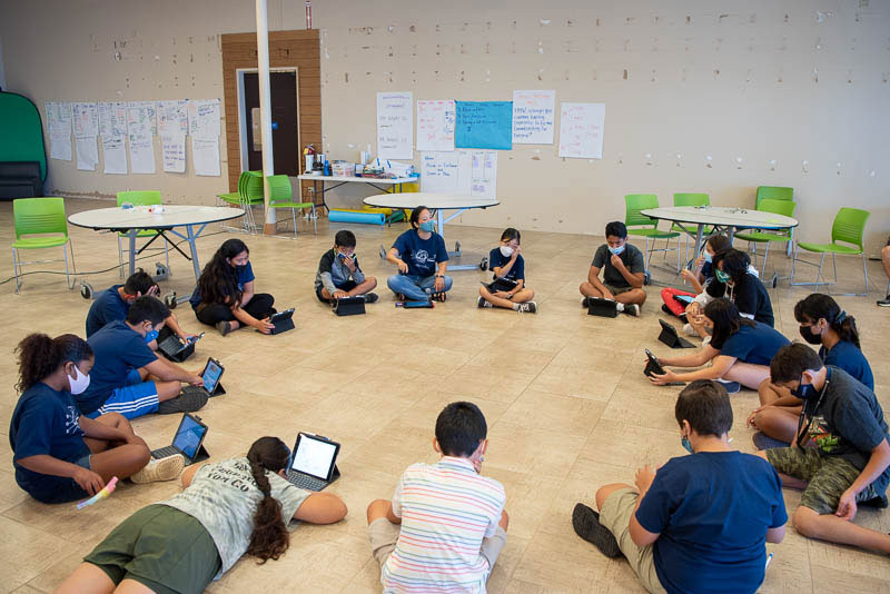 Students sitting in large circle on the floor.