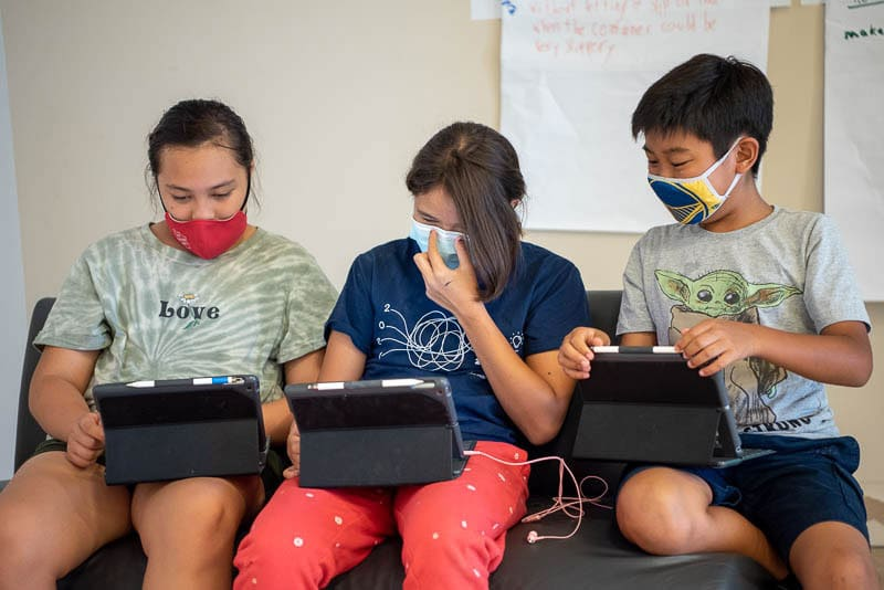 Three students working together on iPads.
