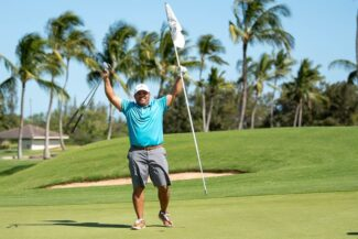 Golfer holds pin and clubs above his head in celebration