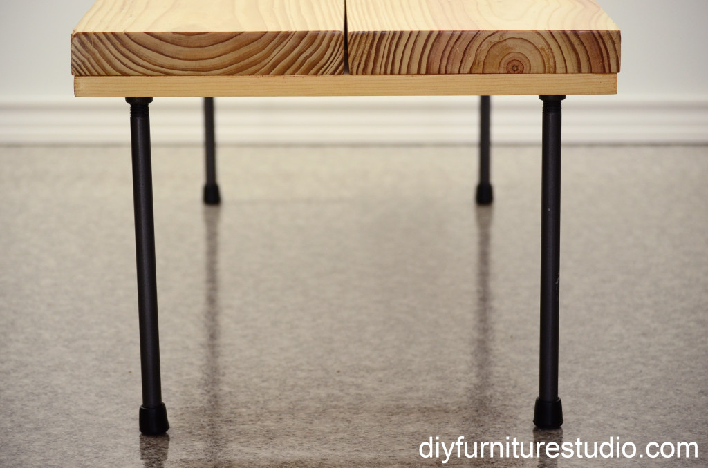 DIY rustic modern coffee table or bench with plumbing pipe legs. View from one end.