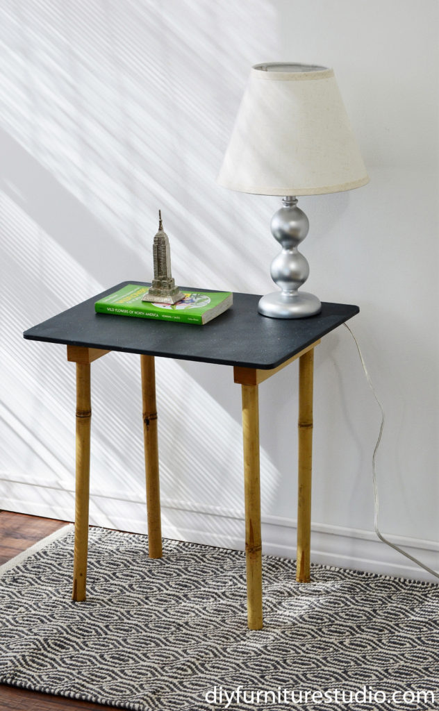 DIY side table made with upcycled bamboo garden stake legs.  I paired the bamboo legs with an interesting plastic cutting board as the table top.