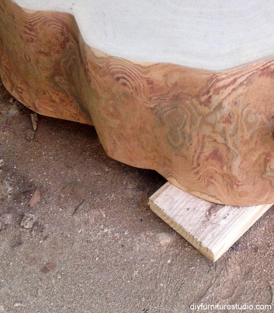 sanding sides of wood slice after removing bark