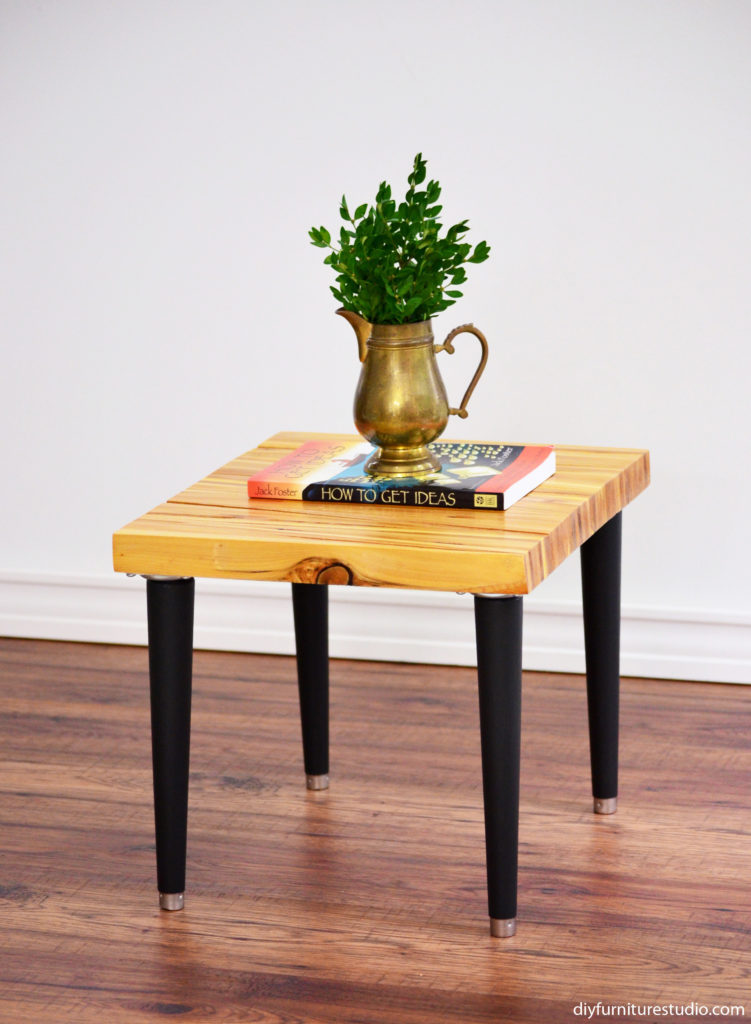 DIY side table made with an upcycled wood shim table top and modified Waddell mid-century modern tapered table legs painted black.