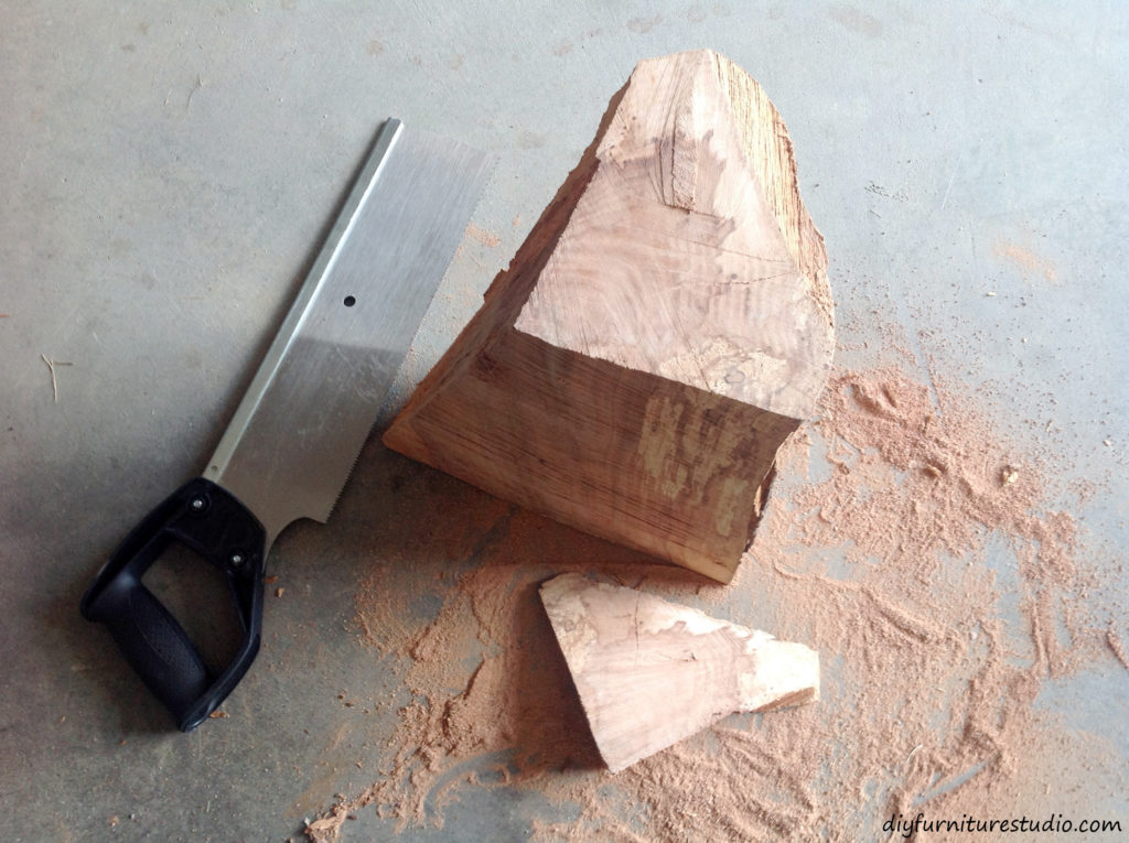 DIY natural wood table lamp. Cutting the top level with a saw.