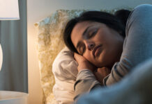 Woman sleepin in bed with side table lamp on