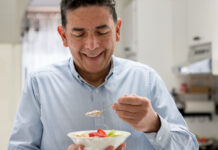 Man eating fruit from a bowl