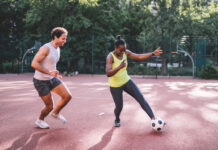 young sportsman and woman playing soccer on hardcourt