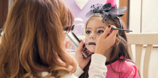 Mother applying make-up on daughter for Halloween