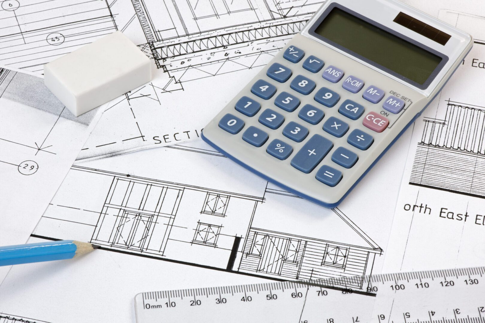 Calculator,rubber,pencil and ruler on architectural drawings. Plans are copyright-free