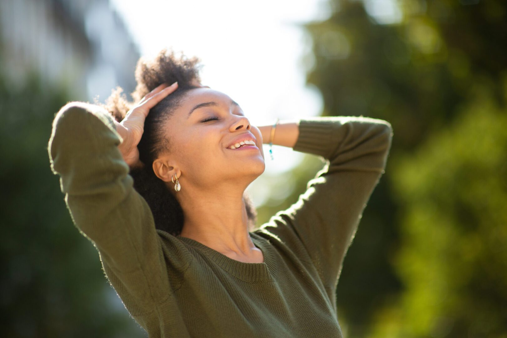 Close up portrait carefree young black woman smiling outdoors with hand in hair