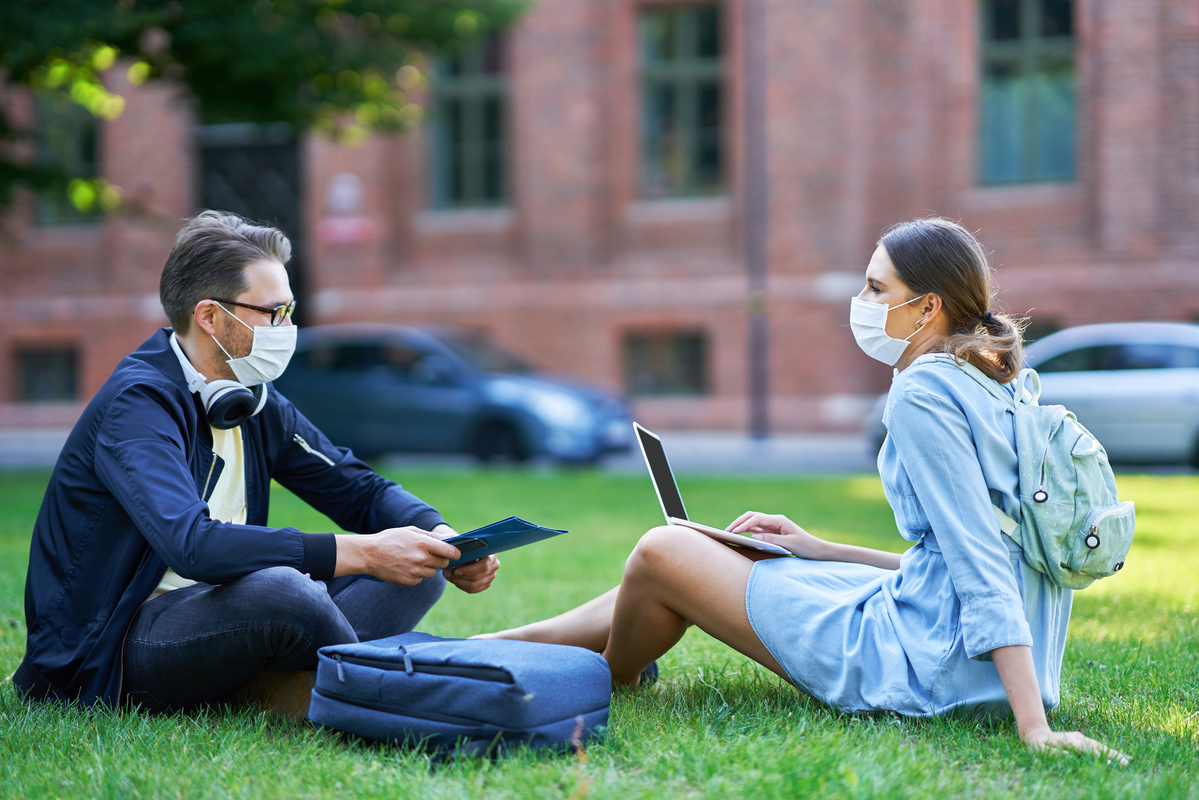 young adults on college campus wearing masks talking and working outside on laptops
