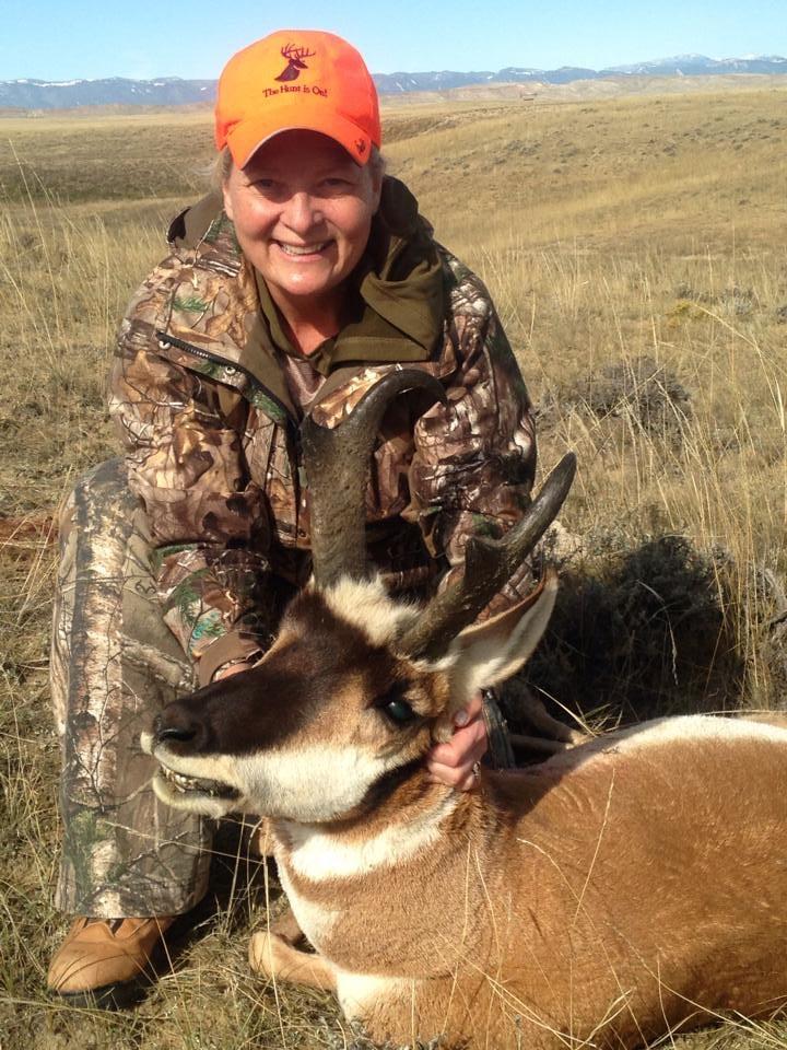 A female hunter holding an antelope