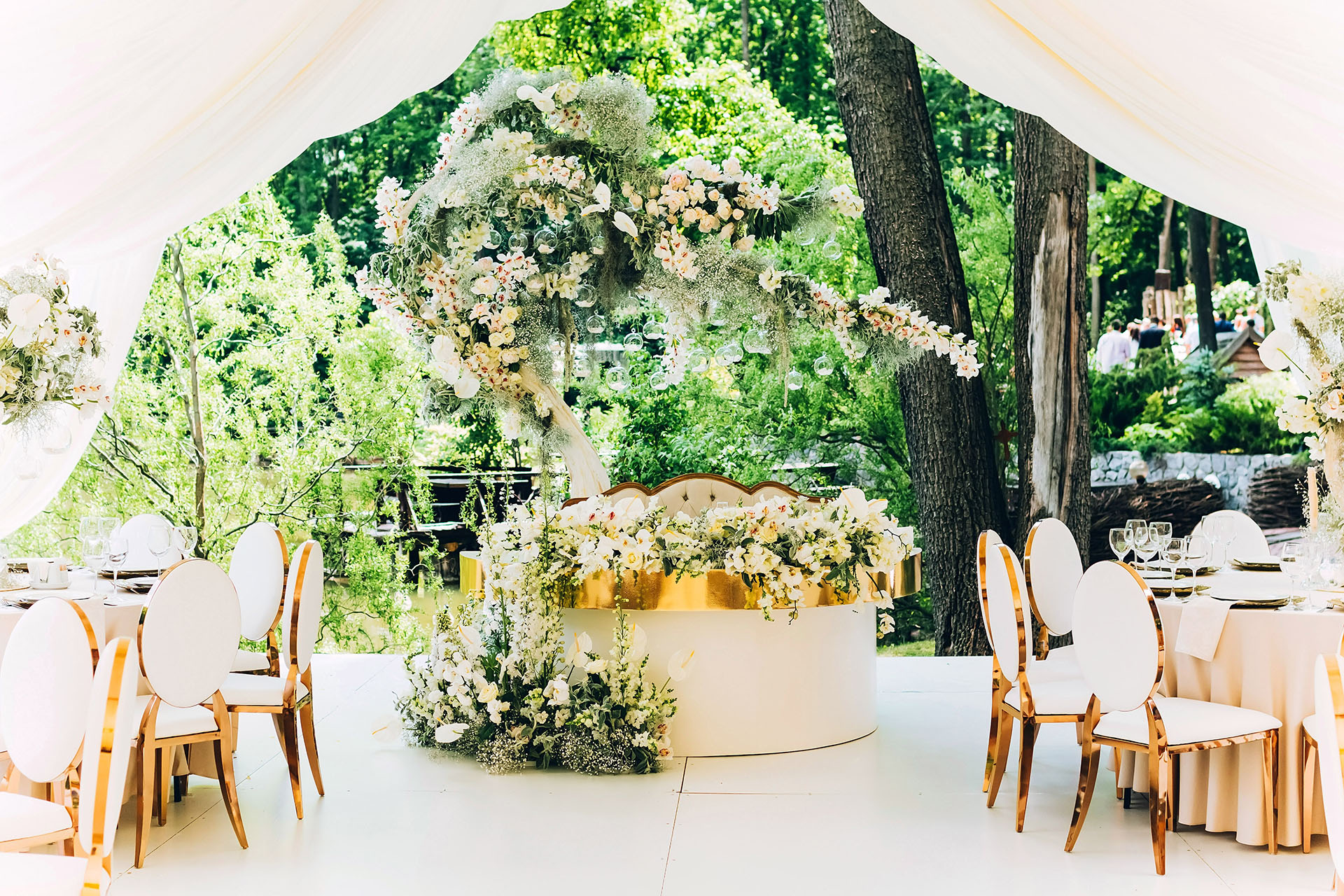 luxury wedding decor. Wedding in white and gold colors. elegant wedding decorated with white flowers. tropical flowers.  white tent. white table of the bride and groom.