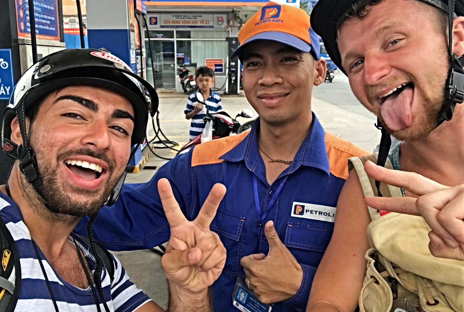 Two tourists taking a photo with employee of a gas station in Southeast Asia