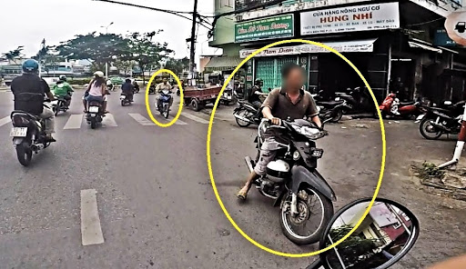 People driving scooters in the opposite side of the road in Southeast Asia