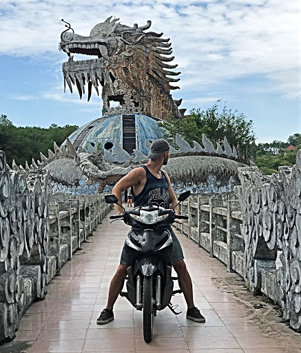 A man on a scooter with a dragon in the background in Ho Thuy Tien waterpark in Vietnam