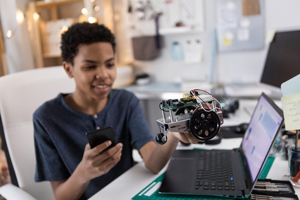 Preteen boy uses smart phone to control robot