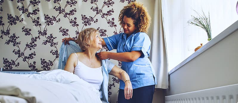 caregiver helping the elderly woman to dress up
