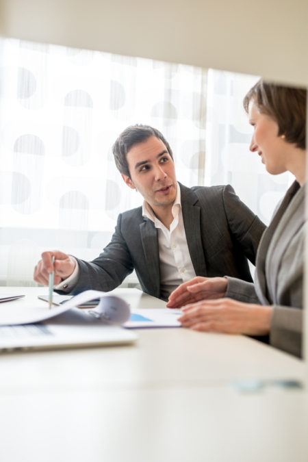 Two Young Business People in Corporate Attire Discussing Some Plans at the Table with Plenty of Documents.