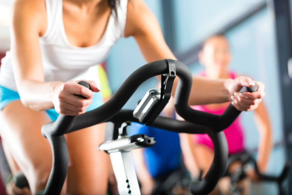 Young People - group of women and men - doing sport Spinning in the gym for fitness