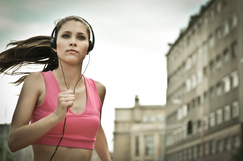 Person (young beautiful woman) listening music running (jogging) in city street