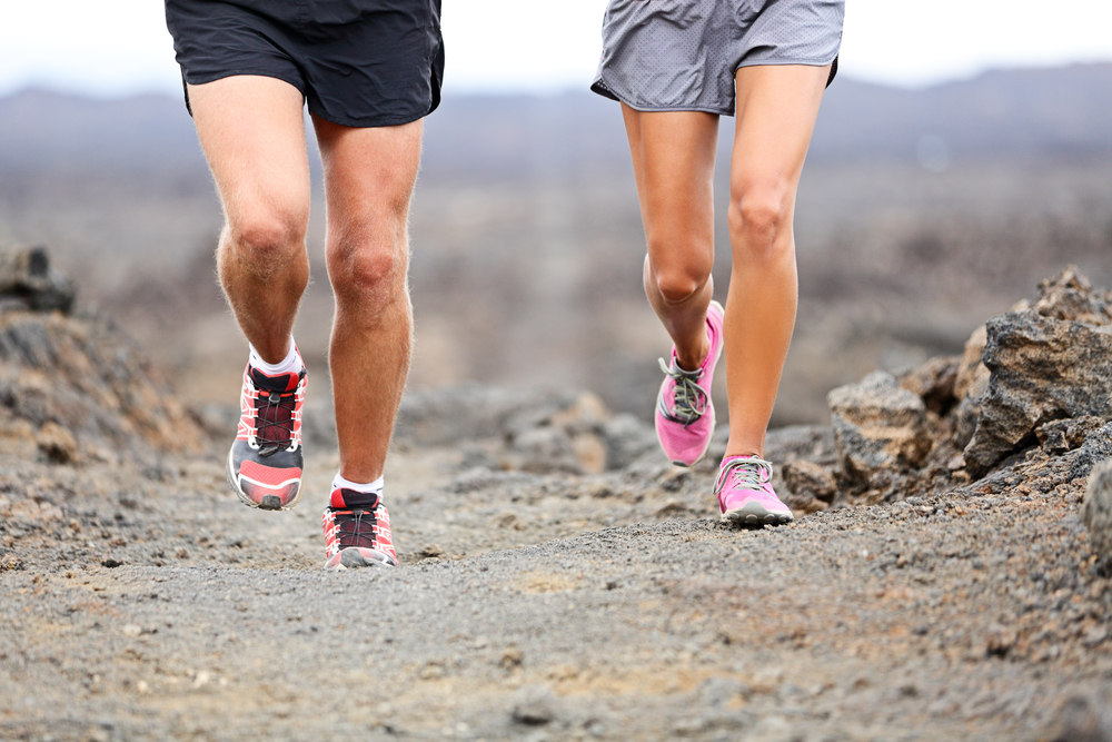 Trail running - close up of runners shoes and legs of athletes exercising and cross-country running outside on rocks on volcano path. Woman and man lower section closeup.