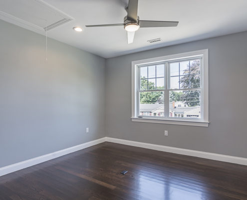 Large room with hardwood floors and window with a view