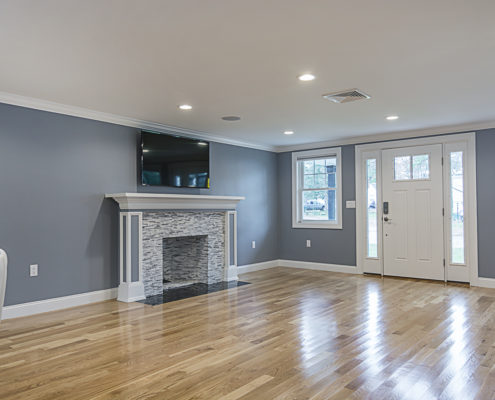 Large entryway with custom fireplace and mounted television