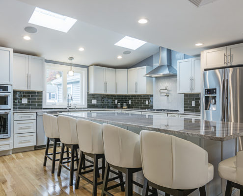 Kitchen with large island and a stainless steel refrigerator