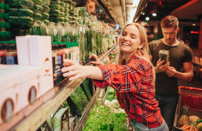Young couple in grocery store. Woman reach ahnd to box and smile. Man stand behind and look at parsley in hands