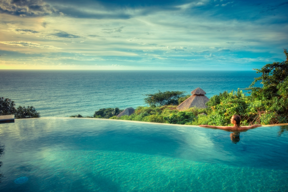 A women in an infinity pool overlooking the ocean in Mexico