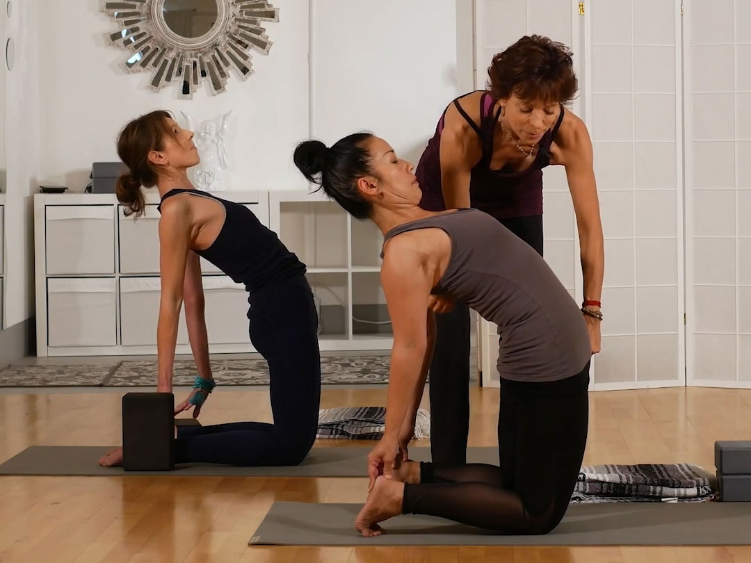 Two people in yoga class with Jeanne Heileman assisting