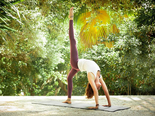Jeanne outdoors on mat lift leg in backbend yoga pose
