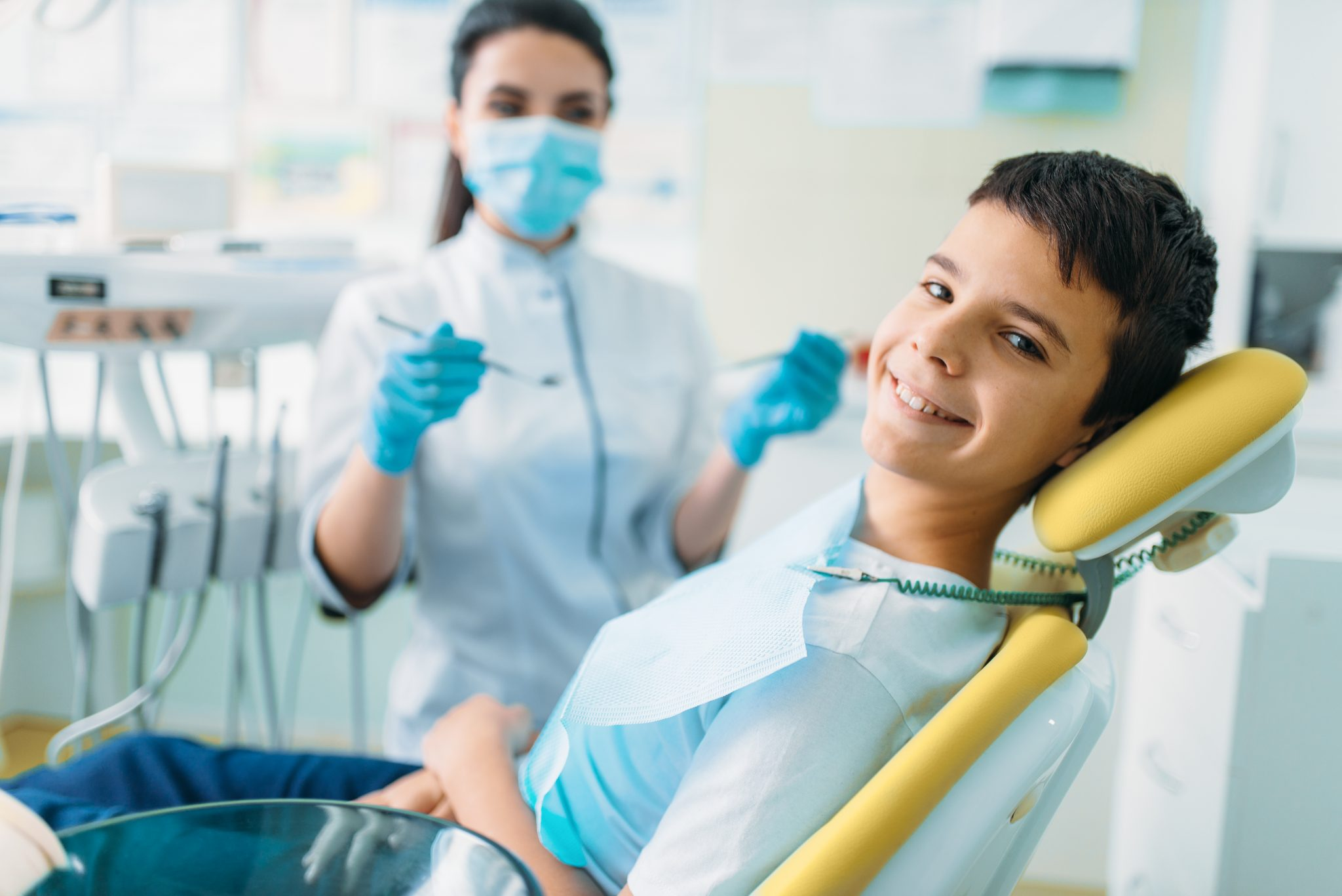 Smiling little boy in a dental chair, professional pediatric dentistry, children stomatology, female dentist on background