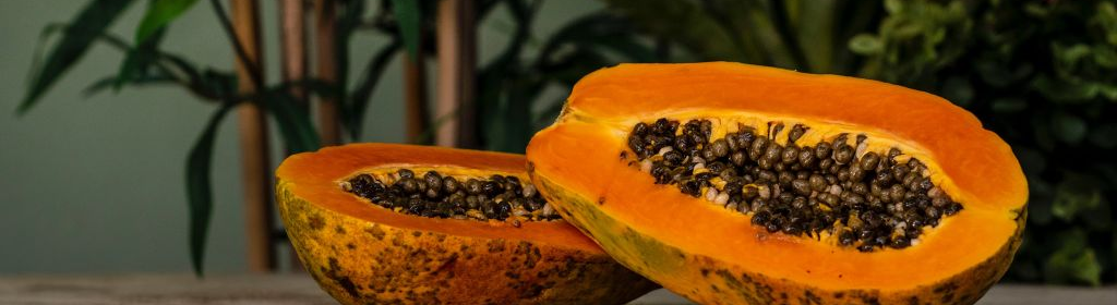 A ripe papaya cut in halves, showing the yellow-orange pulp and black seeds within, on a table.