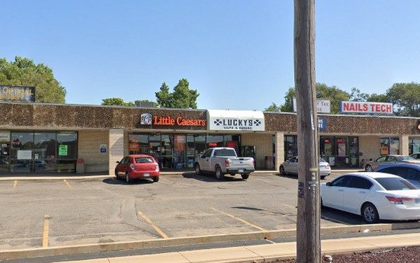 Little Caesars in Wichita inspection; Two small cockroaches crawled around bag of pink sanitizer, larger cockroach crawled around on the floor and along the wall connected to the 3 vat sink