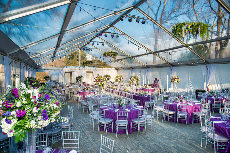 Wedding reception set up underneath a clear top tent.