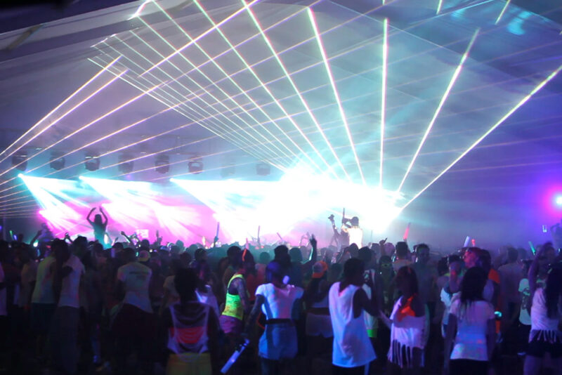 Crowd of people at a concert inside a giant tent.